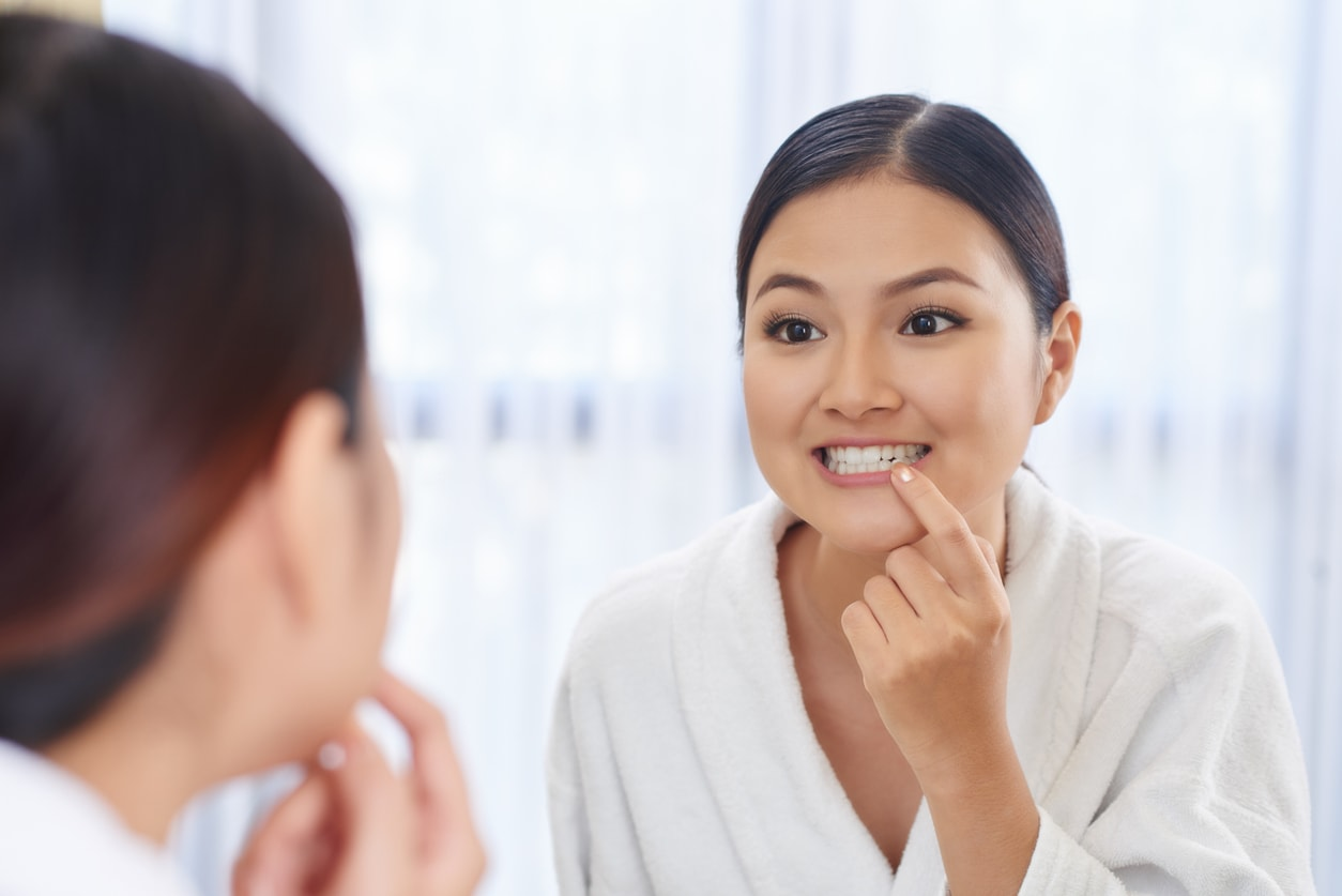 Young woman looking at her teeth in the mirror